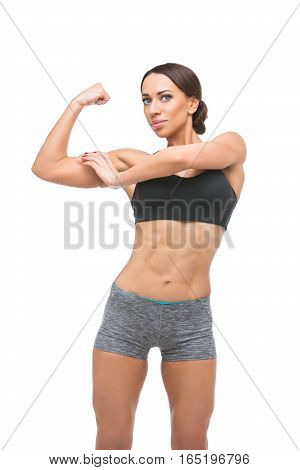 Beautiful fit muscular young woman in sport bra and shorts touching biceps isolated on white background. Perfect body. Studio shot. Copy space.