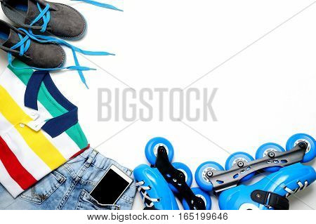 Sport, healthy lifestyle, roller skates and boy's clothing set, cell phone on white background. Street culture layout desk, flat lay space for text