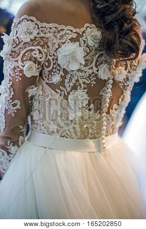 Detail of a wedding dress decorated with crystals lace and veils.