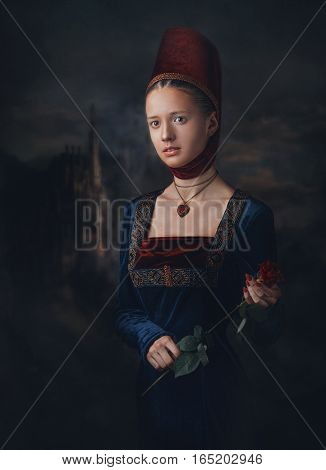 Portrait Of A Gorgeous Girl In Medieval Era Dress And Headdress. Medallion In A Shape Of Heart. Hold