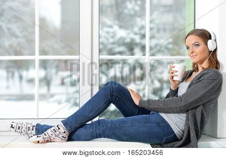 Beautiful girl in headphones drinking tea sitting on windowsill