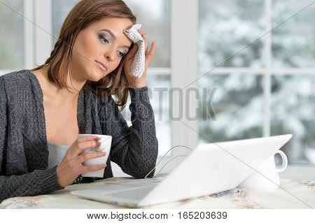 Sick beautiful girl sitting at the table with laptop and drinking tea