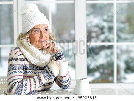 beautiful smiling mature woman drinking tea, sitting near window