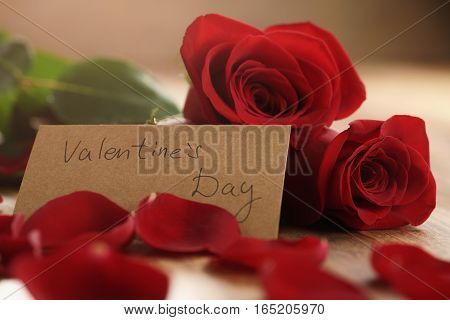 three red roses with petals on wood table and paper card for valentines day, closeup photo