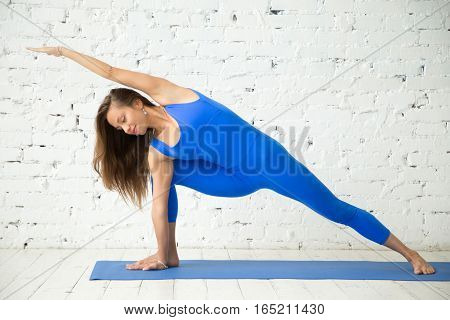 Young happy attractive woman practicing yoga, standing in Extended Side Angle exercise, Utthita parsvakonasana pose, working out, wearing sportswear, blue jumpsuit, indoor full length, white studio