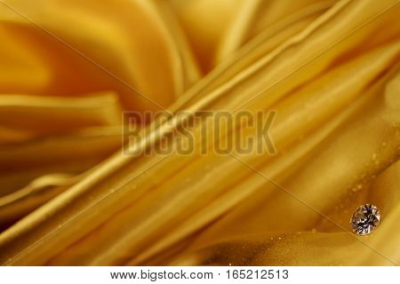 Beautiful big diamond jewelry on golden satin cloth background. Fine natural precious stone
