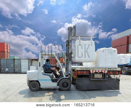 Forklift driver moving big bag to the truck at yard.