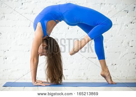Woman practicing yoga, standing in One legged Wheel exercise, Bridge pose, working out, wearing sportswear blue suit, indoor full length, white loft studio background. Tattoo on foot Way of heart