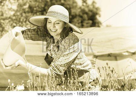 Gardening. Attractive woman in hat working in her backyard garden watering flowers outdoor
