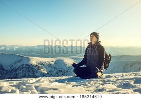 man hikers tourists sitting meditating after a hard ascent alone feeling the freedom at the top at the peak of a snowy mountain at sunset the concept of the path to purpose and success