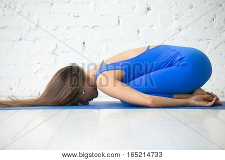Young attractive woman practicing yoga, sitting in Child exercise, Balasana pose, working out, wearing sportswear, blue suit, indoor full length, white loft studio background