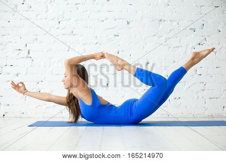 Young happy attractive woman practicing yoga, stretching in variation of Bow exercise, Dhanurasana pose, working out, wearing sportswear, blue suit, indoor full length, white loft studio background