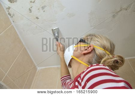 Blonde woman holding a plaster spatula peeling a ceiling preparing it for smoothing