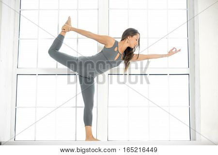 Young attractive woman practicing yoga, standing in Lord of the Dance exercise, Natarajasana pose, working out, wearing sportswear, grey suit, indoor full length, window studio background
