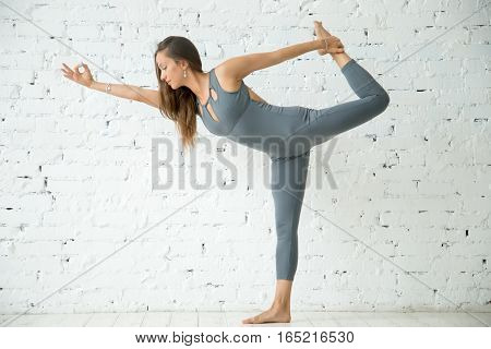 Young attractive woman practicing yoga, standing in Natarajasana exercise, Lord of the Dance pose, working out, wearing sportswear, grey suit, indoor full length, white loft studio background