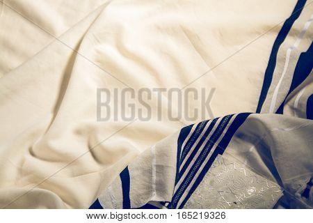 Talit - jewish prayer shawl with hebrew text, element of prayer vestments. Toned image