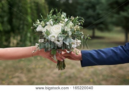 groom gives the bride a beautiful bridal bouquet.