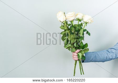 Bouquet of white roses in hands. Valentine's day.