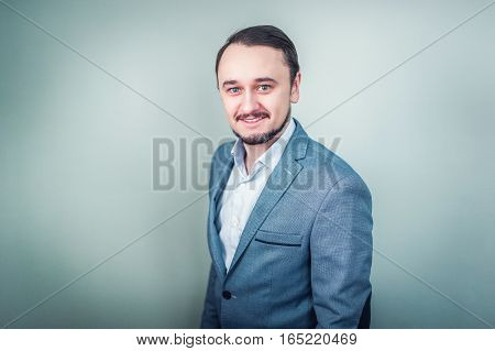 Portrait of a young businessman on grey background.