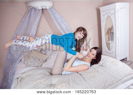 Happy Mother And Daughter Lay In Bed And Having Fun.