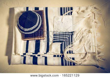 Jewish ritual objects, elements of prayer vestments, Talit with hebrew text, Kippah and Siddur - jewish prayer book. Toned image