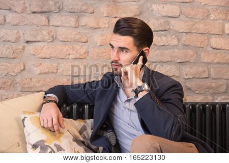 Young Man Indoors Talking Phone Sitting