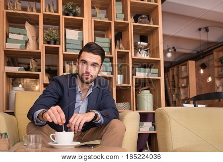 Young Man Stirring Coffee Cup Indoors Caffee Bar