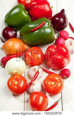 Vegetables. Peppers, tomatoes, garlic, onions, eggplant, cucumber and radishes on a white wooden background