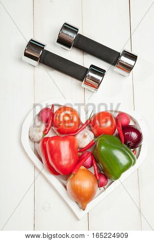Sport and diet. Healthy lifestyle. Vegetables, dumbbells. Peppers, tomatoes, garlic, onion and radish in a heart on a white background