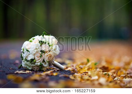 bouquet of roses for bride on the autumn leaves in a forest