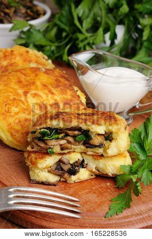Potato cakes (zrazy) Stuffed mushrooms with herbs of the table with sour cream
