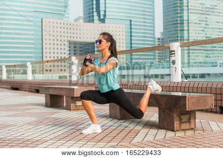 Sporty female athlete doing single leg lunge exercise on bench. Fit young woman working out outdoors in city alley.