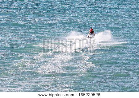 Jet ski rider on sea water splashing outdoor daylight