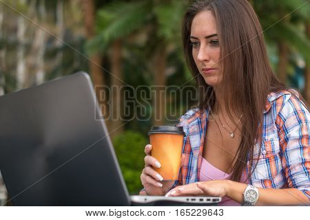 Young woman typing on her laptop working and drinking coffee in the park.