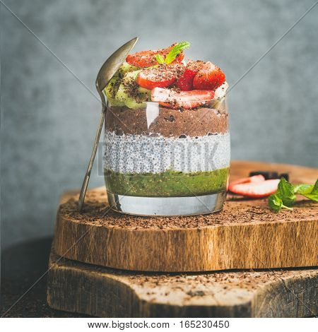 Healthy breakfast. Matcha, almond milk, cocoa chia seed pudding with fresh fruit, berries, mint, chocolate in glass over wooden board, grey wall background, selective focus, square crop, copy space