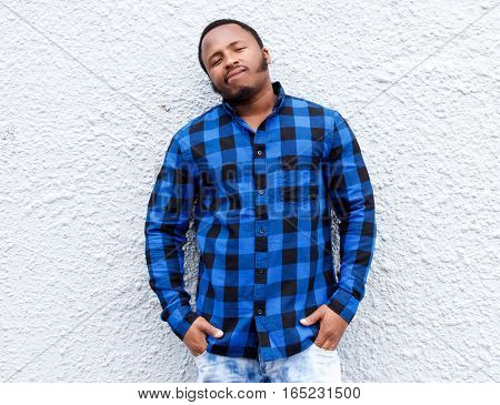 African American Man In Blue Shirt Standing Against White Wall