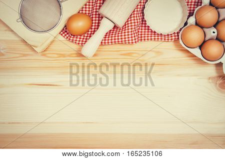 Baking a cake or pizza ingredients background. Top view photograph with kitchen utensils on vintage, natural, raw, wooden background with visible texture.