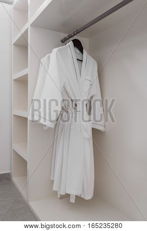 white bathrobe with wooden hangers in wardrobe.