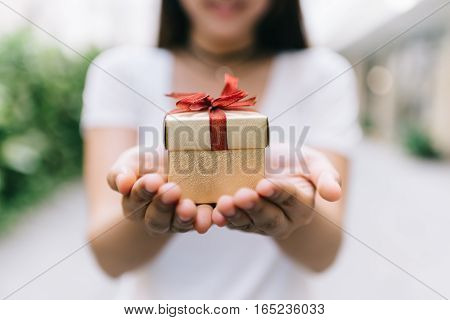 Young Asian woman showing gift box in her hand