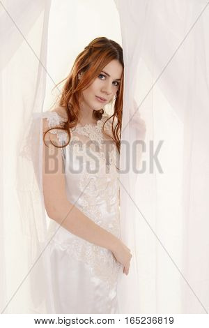 portrait of red head bride holding window curtains