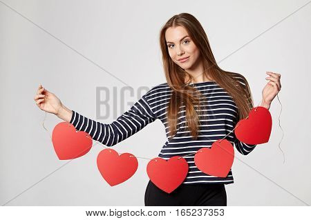Beautiful smiling woman holding garland of five red paper hearts shape - blank copy space for letters or text