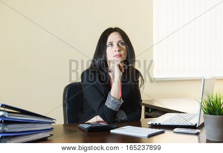 Young attractive woman in a business suit behind a Desk in the office looks at the ceiling