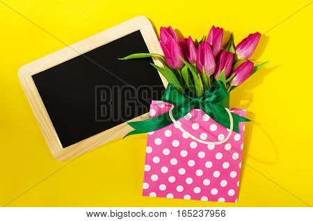 Fresh beautiful lila tulips in gift package on bright yellow background with chalkboard. Spring concept. Horizontal top view with copy space.