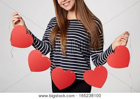 Croped image of a woman holding garland of five red paper hearts shape - blank copy space for letters or text
