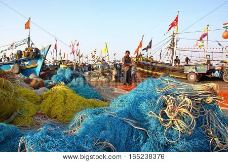 DIU, INDIA - JANUARY 9, 2014: Fisherman working on his net at Vanakbara Fishing port with colorful fishing nets in the foreground