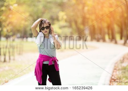 Asian executive mature woman runner taking a rest after running hard in countryside road. sweaty athlete after marathon training in country road and talking with smartphone