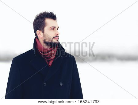 Fashion portrait handsome elegant bearded man wearing black coat winter over snowy background looking away distance empty copy space