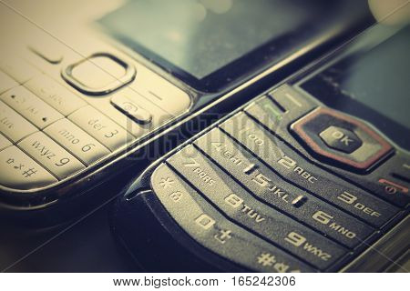 Two push button phones on a white background.