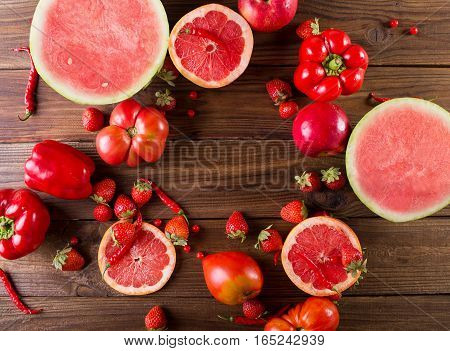 Red fruits and vegetables on a wooden background. Colorful festive still life.