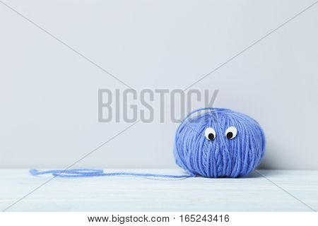 Ball Of Yarn With Googly Eyes On A Grey Background